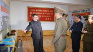 Igicucu cya Kim Jong-un kigaragara ku gishushanyo cya misile izwi nka Hwasong-13 mu gihe abandi bategetsi bakingirije igishushanyo cy'indi misile itererwa mu bwato bugendera mu nsi y'inyanja