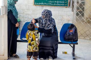 Gulnaz vaccinating a child