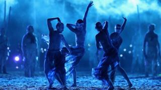 A tribe performs a traditional dance against bright blue light.