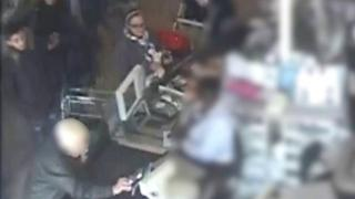 CCTV footage of people watching woman enter her pin code in supermarket