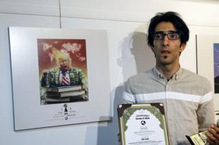 Iranian cartoonist Hadi Asadi poses for a picture with a trophy and an award next to cartoons of US President Donald . Trump, at an exhibition of the Islamic Republic's 2017 International Trumpism cartoon and caricature contest, in the capital Tehran on 3 July 2017.