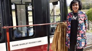 Dame Shirley Bassey in front of a Snowdon Mountain Railway carriage