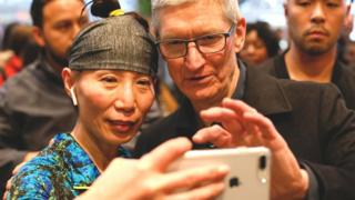 A woman takes a selfie with Apple chief executive Tim Cook