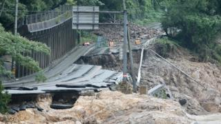 A road is destroyed following torrential rain near the Kuma river in Ashikita, Kumamoto prefecture, on July 6, 2020