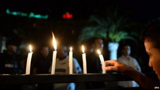 A boy arranges candle lights on a fence in front of the Hotel Imperial Marhaba in Sousse, Tunisia