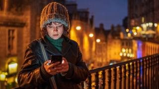 Woman looking at phone in Edinburgh