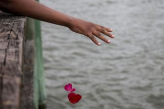 A woman's hand is seen throwing pink and red petals into the sea.