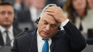 Hungary's Prime Minister Viktor Orban places his hand on his head in an emotive gesture