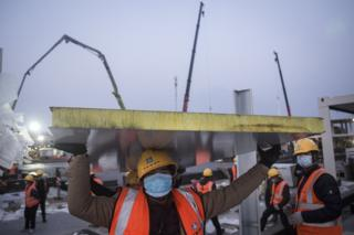 A construction worker is pictured amidst heavy machinery on the site of Huoshenshan hospital, under construction
