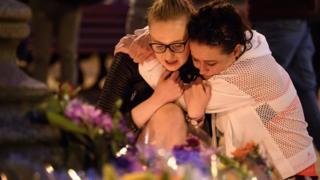 Dos mujeres se abrazan frente a los homenajes a las víctimas del atentado en Manchester.
