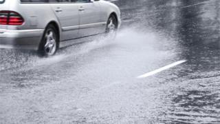 Car drives through surface water