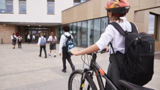 girl-wheeling-bike-into-school