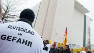 """""""Germany in danger"""" is written on the T-shirt of a protester outside the German chancellery"""