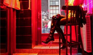 A German prostitute waits for clients behind her window in the red light district of Amsterdam in 2008