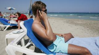 man on phone on beach