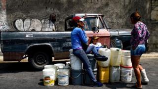 Mujeres en Venezuela esperando para llenar tanques de agua.