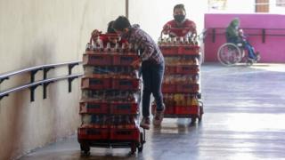 Workers carry sodas while wearing protective masks on May 9, 2020 in Queretaro , Mexico.