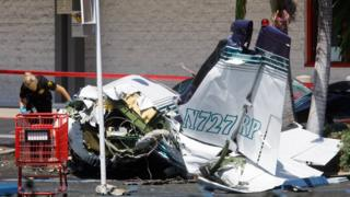 An investigator looks over the wreckage of a small plane that crashed into a strip mall parking lot in Santa Ana