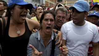 A woman standing outside validation centre to certify her signature becomes angry after learning that it closed at appointed hour, without attending those still waiting, in Caracas, Venezuela, Friday, June 24, 2016