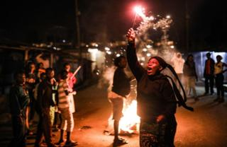 A woman holds a sparkler during New Year celebrations in the Kibera slum in Nairobi on January 1, 2019