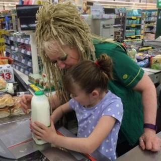 Cashier Lin helps Amanda's daughter to scan the family's shopping