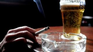 Someone holding cigarette next to pint of beer