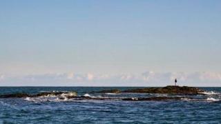 Bear Grylls' son Jesse stands on rocks off Abersoch