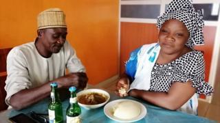 """Des clients d'un restaurant en train de déguster un plat de """"pâte"""" fait à base de farine d'ignames séchées."""
