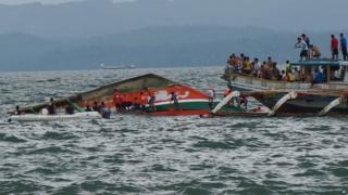 Rescuers help passengers from the capsized ferry (02 July 2015)