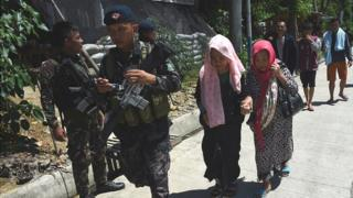 Philippine policemen walk with evacuees from Marawi at a checkpoint on the southern Philippines island of Mindanao