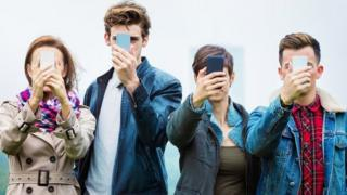 4 people holding their smartphones in front of their faces