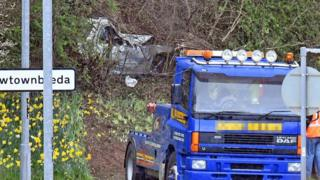 A silver Mercedes car crashed in undergrowth, with a vehicle recovery lorry parked nearby