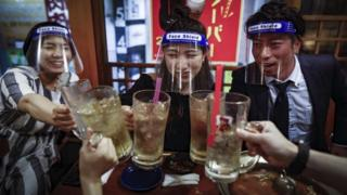Customers wear plastic face shields as they toast their glasses in Osaka, Japan