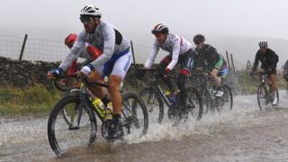 Cyclists ride through flooded race route on Cray Summit