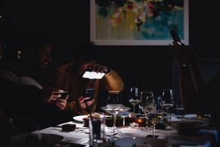 Two men take photos of the their food in a restaurant