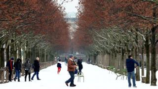 People walk in the snow-covered Tuileries Garden in Paris, as winter weather hits the city on 22 January 2019