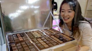 Mulher japonesa observa bandeja de bombons de chocolate