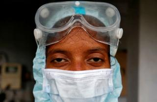 in_pictures Beads of sweat run down the forehead of a healthcare worker wearing protective gear