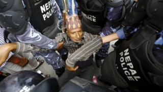 A Hindu activist blocking a road is carried away by police during a protest rally demanding Nepal be declared a Hindu state in the new constitution, near the parliament in Kathmandu, Nepal, September 1, 2015