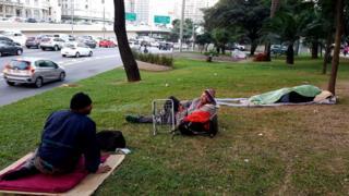 Amigos dormindo em gramado na frente da estação Anhangabaú
