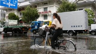 A woman cycles through a flooded area in Tokyo