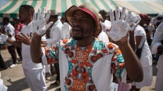 Supporters of the Gabonese opposition leader Jean Ping, dressed in white and with their hands painted in white as a sign of peace, take part in a commemoration march outside the party's headquarters in Libreville, Gabon - Saturday 10 September 2016
