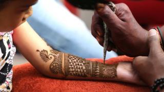 Msichana akipakwa tatuu ya Henna mkono wake kwa jili ya sherehe za Idd al Adha katika jimbo la India la Kashmir