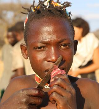 Hadza child eating red meat