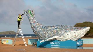 Jordan Asil puts the finishing touches to a 10-metre long whale unveiled by Sky Ocean Rescue at Newquay, Cornwall,