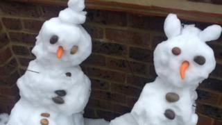 Two snowmen with carrot noses.