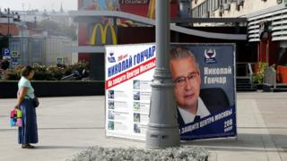 A woman looks at the United Russia political party's campaign poster promoting candidate Nikolai Gonchar in central Moscow