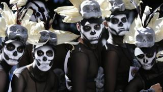 Men dressed in costumes wait for a Day of the Dead parade to begin along Mexico City's main Reforma Avenue, Saturday, Oct 29, 2016
