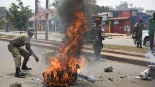 Uganda's military police intervenes near a burning barricade on February 19, 2016 in Kampala.