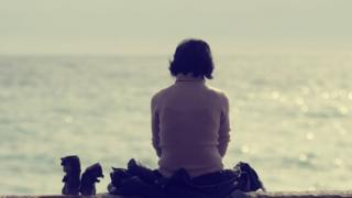 Stock image of a woman sat by the sea